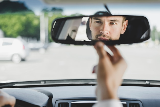 Man looking back through the rear view mirror from the front seat of a car