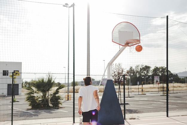 Man looking at basketball going through hoop