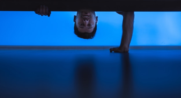 The man looking under the bed. evening night time