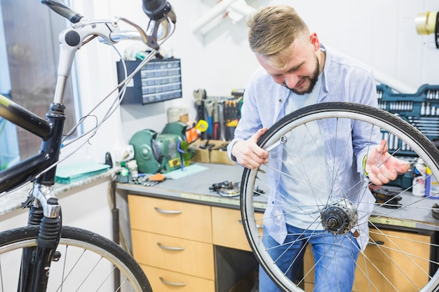 Man looking at bicycle tire in workshop