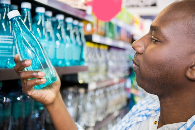 Man looking at bottle of water