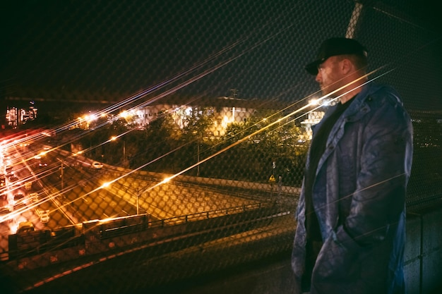 Man looking at busy city highway at night on the bridge