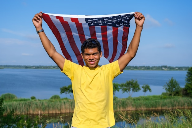 Man looking at camera and proudly holding american flag in his arms