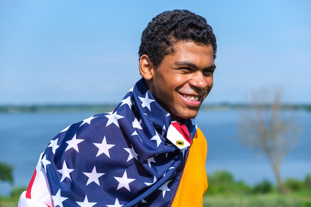 Man looking at camera and proudly holding american flag on his shoulders