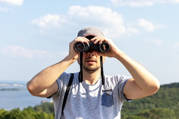 A man looking at camera through binoculars against a scenic view of a wide river on a hill on a sunny day