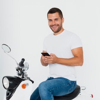 Man looking at camera and typing on his mobile phone