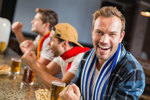 Man looking at camera while other men cheer for the game
