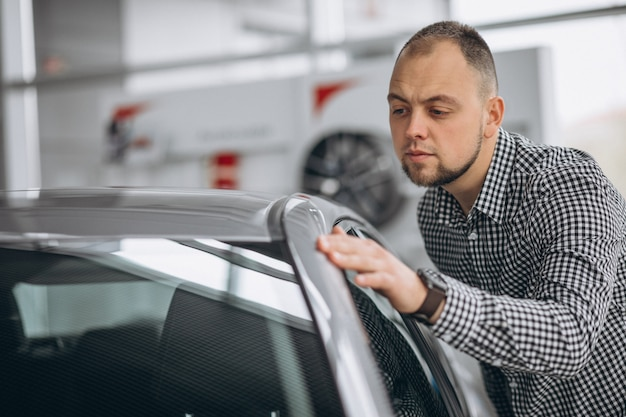Man looking at a car in a car showroom