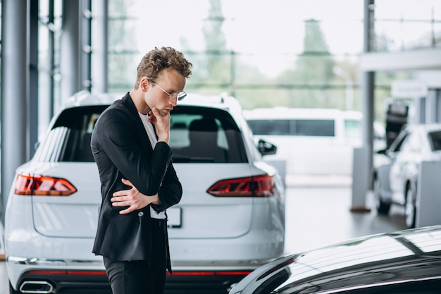 Man looking at a car and thinking of a purchase