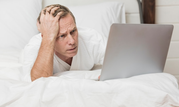Man looking concerned on his laptop in bed