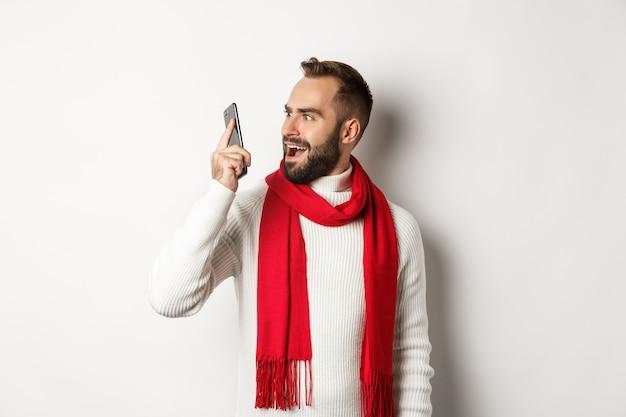 奇妙な声を聞いた後、携帯電話で混乱しているように見える男、ショックを受けたスマートフォンを見つめ、白い背景の上に立っている