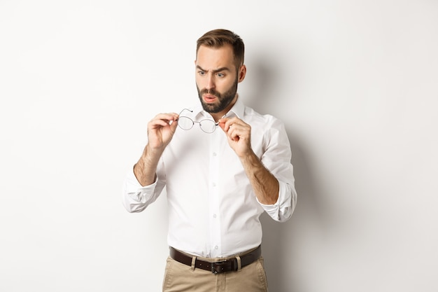 Man looking confused at his glasses, standing in office clothing against white background.