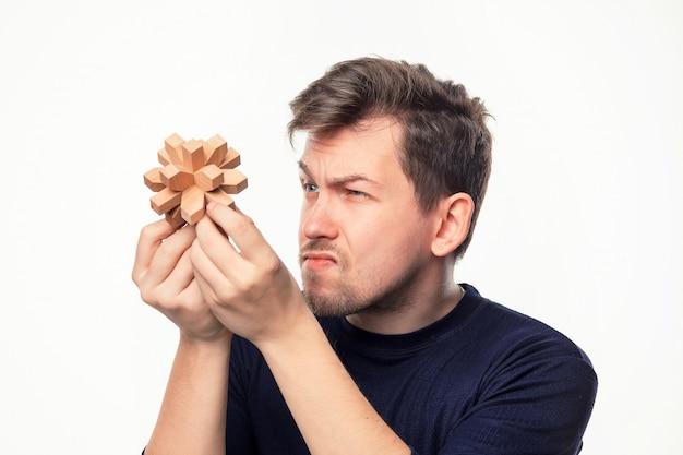 Uomo che sembra confuso al puzzle di legno.