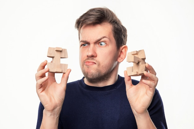 Man looking confused at wooden puzzle.