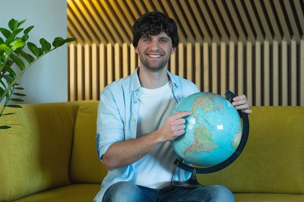 Man looking for countries on globe at home in living room on sofa cheerful man holding a geographic globe