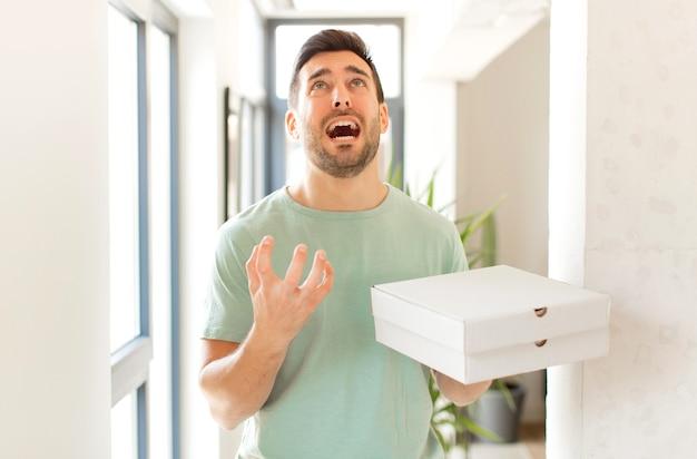 Мужчина выглядит отчаявшимся и расстроенным, напряженным, несчастным и раздраженным, кричит и кричит
