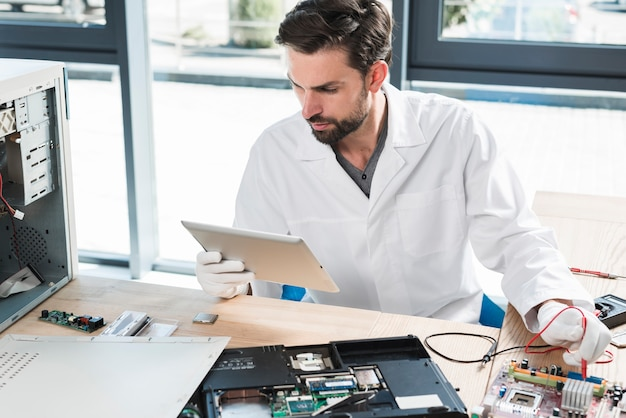 Man looking at digital tablet while repairing computer in workshop