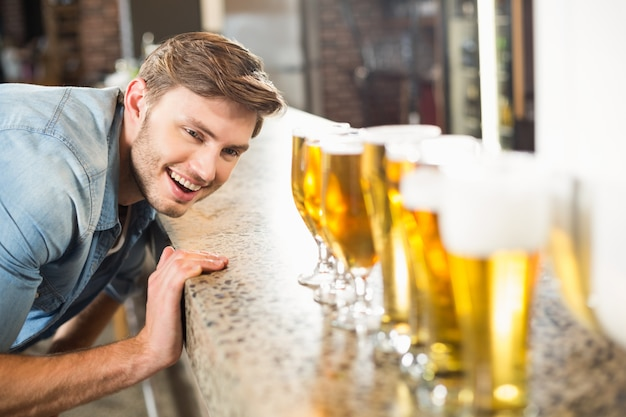 Man looking down lined up beers