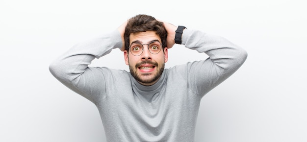 Мужчина выглядит взволнованным и удивленным, с открытым ртом обеими руками на голове, чувствуя себя счастливчиком