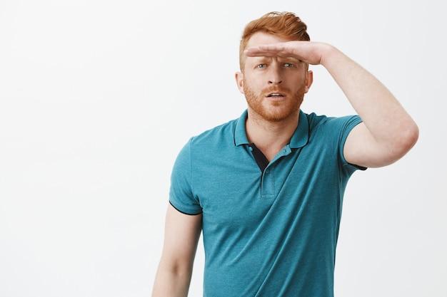 遠くを見ている男性、目を細めて額に手のひらを持って日光から目を覆い、はっきりと見えるように立って、焦点を合わせて立って、灰色の壁にポロシャツを迎えることに興味を持っている