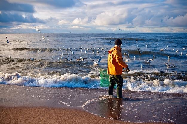 Мужчина ищет янтарь в балтийском море