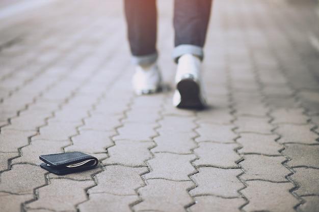 Человек ищет бумажник, лежащий на тротуаре