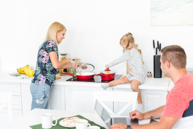 Man looking at her wife and daughter working in the kitchen