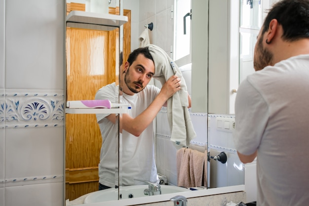 Man looking at himself in a mirror in the bathroom. he is drying his hair with a towel.