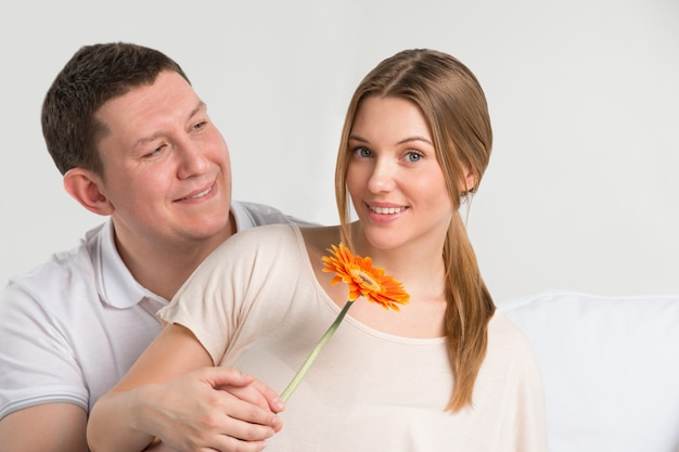 Man looking at his beautiful girlfriend and giving her a flower