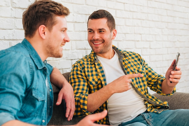 Man looking at his smiling friend pointing his finger on mobile phone