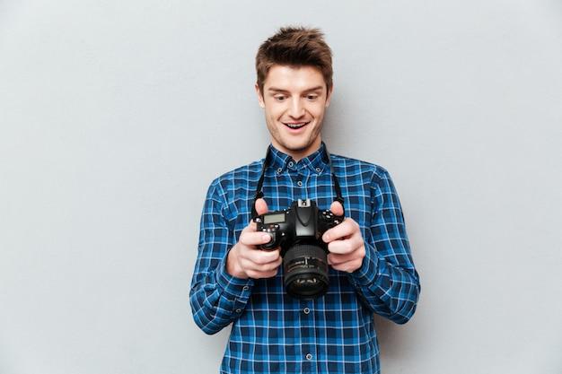 Uomo che guarda le immagini sulla fotocamera e sorprendente
