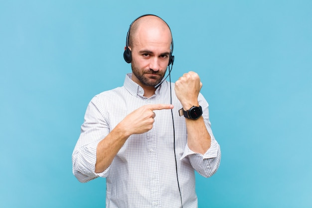 Man looking impatient and angry, pointing at watch, asking for punctuality