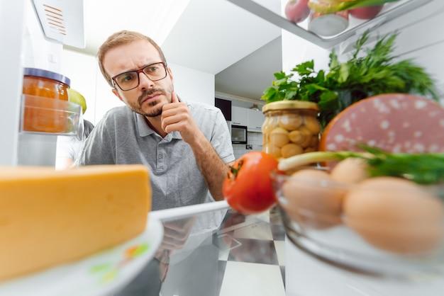 食品の完全な冷蔵庫の中を見ている男。