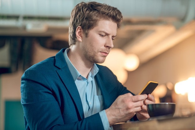 Man looking into smartphone in cafe
