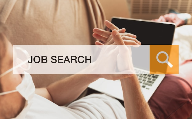Man looking for a job during worldwide crisis. find a job online. business, internet and networking concept. caucasian man looks through vacancies and sends resumes, needs to earn. modern search bar.
