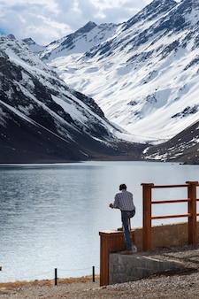 Man looking at the laguna del inca lake surrounded by mountains in chile