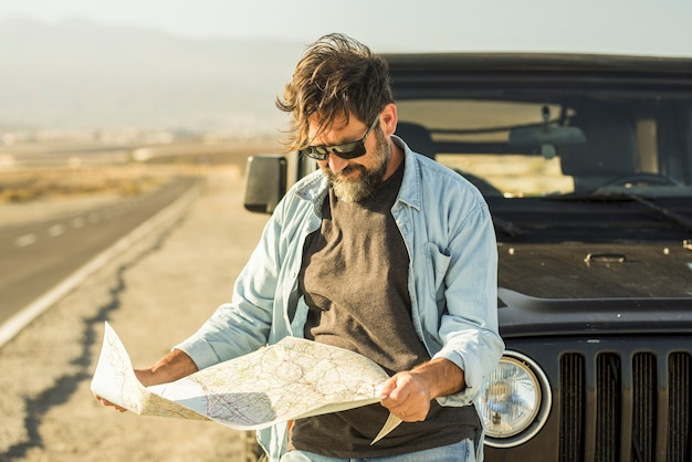 Man looking at map leaning on vehicle at roadside. mature man checking location of destination on paper map standing outside car. man searching for navigational route using paper map at roadside