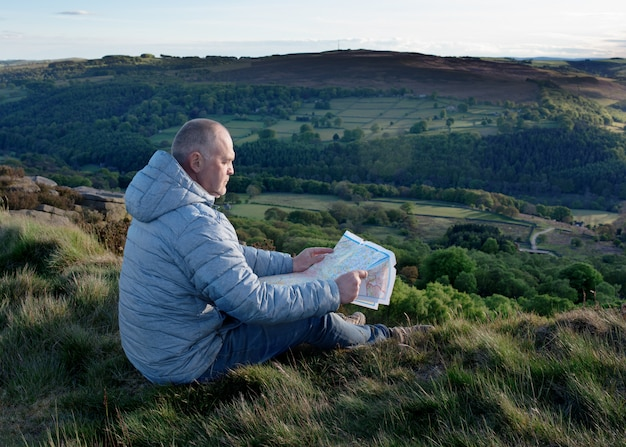 Man looking at map and sitting on the top of mountain