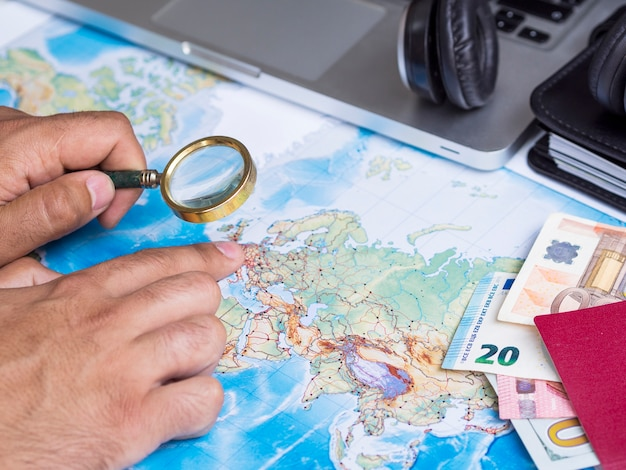 Man looking at a map with magnifying glass