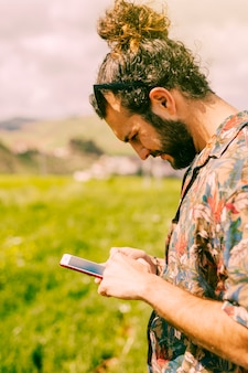 Man looking at mobile phone in field
