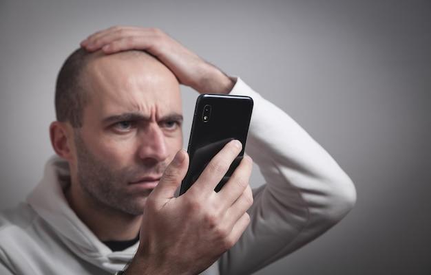 Man looking at mobile phone screen. social media addiction