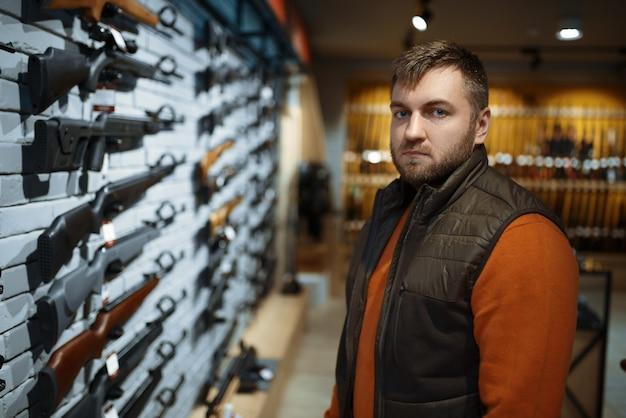 총기 상점에서 쇼케이스에 권총을 찾는 남자