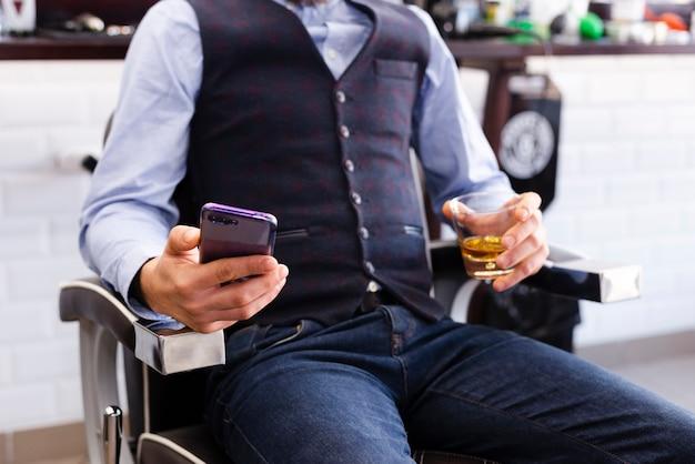 Человек смотрит на свой телефон в парикмахерской