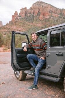 Мужчина смотрит в открытую дверь своего черного спортивного автомобиля
