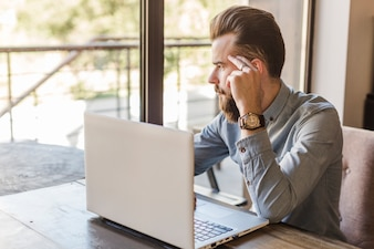 Man looking outside window with laptop on desk in caf�