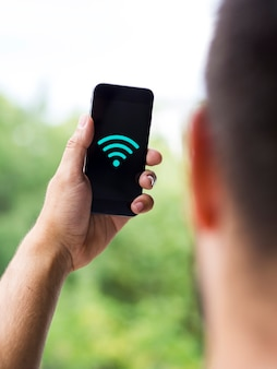 Man looking at phone screen with wifi symbol