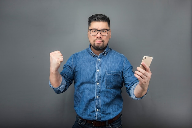 A man looking at the phone with amazement on a gray
