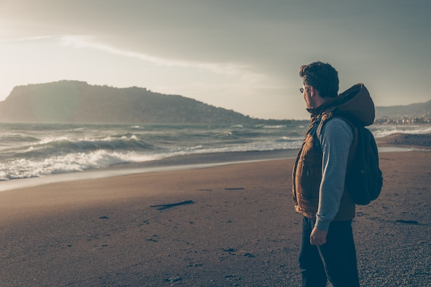 Man looking at sein beach during daytime and looking thoughtful