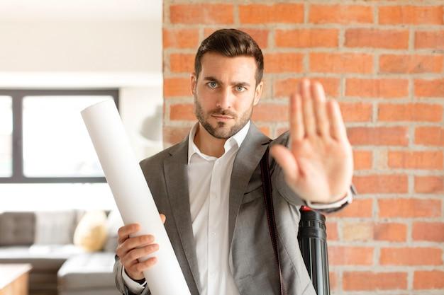 Мужчина выглядит серьезным, суровым, недовольным и злым, показывая открытую ладонь, делая стоп-жест