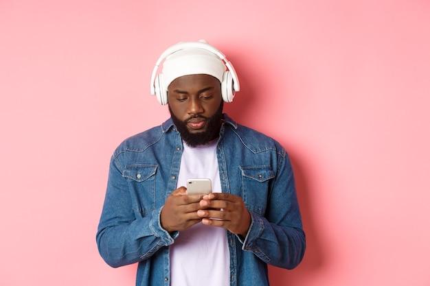 Uomo che sembra serio mentre legge messaggi sul telefono, ascolta musica in cuffia, in piedi su sfondo rosa.